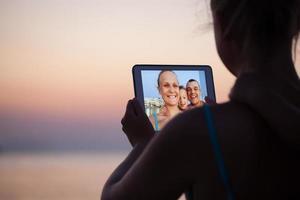 família conectando-se virtualmente em uma praia foto