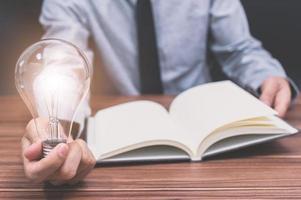 empresário com notebook e lâmpada