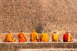 monges budistas sentados em frente à antiga estupa na cidade de Kushiingar, Índia foto