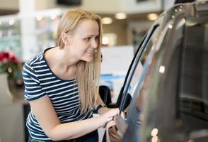 mulher admirando um carro em um salão de automóveis