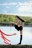 ginasta rítmica em divisão vertical com uma fita foto