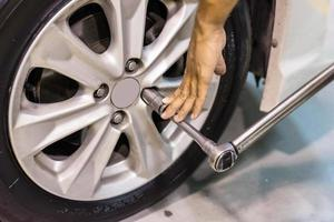 mecânico de automóveis trocando a roda do carro foto