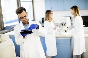 pesquisadores em roupas de trabalho de proteção em pé no laboratório e analisando amostras de líquidos foto