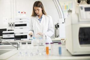 médica usando máscara protetora em laboratório segurando frasco com amostra de líquido