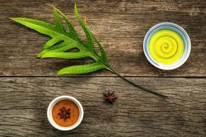 folhas verdes e com óleo aromático e anis estrelado em fundo rústico foto