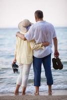 casal se abraçando e olhando para o mar foto