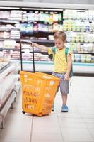 menino com um carrinho de compras na loja