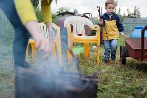 mãe e filho acendendo fogo no quintal