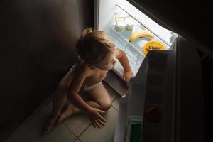 garotinho sentado perto de uma geladeira aberta à noite