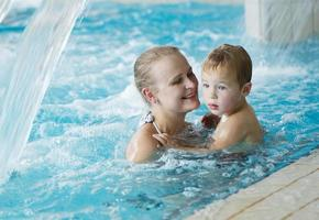 mãe e filho em uma piscina foto