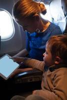 mãe e filho viajando de avião foto