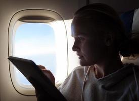 mulher com um tablet em um avião