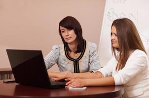 duas mulheres sentadas em uma mesa com um laptop