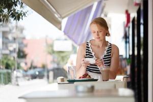 mulher em seu telefone em um café ao ar livre