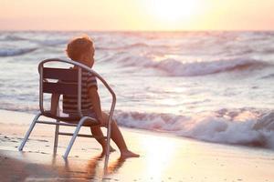 menino sentado em uma cadeira à beira-mar