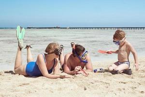 pais e filhos em snorkels brincando na praia