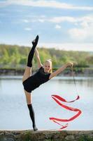 ginasta adolescente fazendo uma divisão vertical com uma fita foto