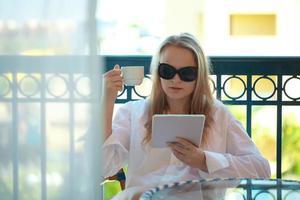 mulher usando um tablet e segurando um café foto