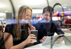 homem e mulher usando um tablet em um café foto