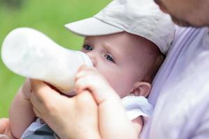 homem alimentando bebê com mamadeira