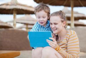 mãe e filho felizes em um resort de praia com um tablet