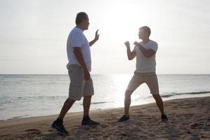 dois homens treinando na praia