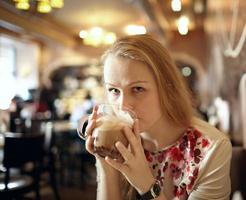 mulher bebendo café com leite em uma cafeteria