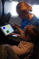jovem mãe e filho viajando de avião foto