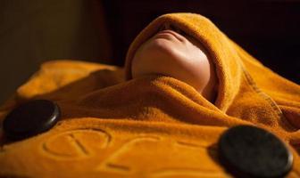mulher recebendo tratamento com toalha quente no spa de beleza