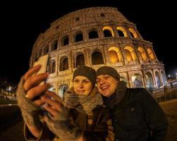 casal feliz tirando uma selfie em frente ao coliseu foto