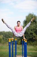 ginasta atlética se exercitando em barras paralelas foto
