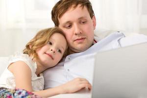 filha e pai usando um laptop