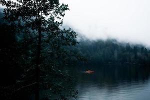 barco laranja em um lago nebuloso foto