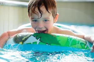 menino com uma boia em uma piscina foto
