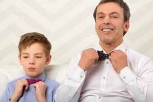 pai e filho ajustando gravatas-borboleta