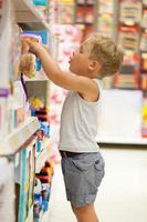 menino escolhendo um brinquedo em uma loja foto