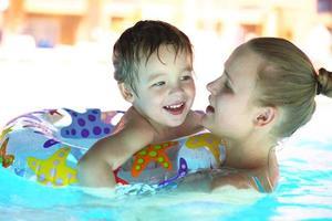 mãe e filho em uma piscina ao ar livre foto