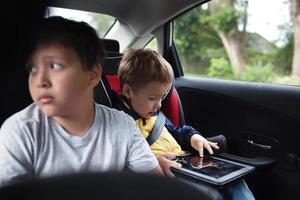 dois meninos no banco de trás de um carro