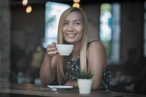 linda mulher em um café tomando café foto