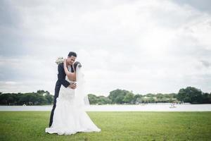 linda noiva e lindo noivo postando na natureza foto