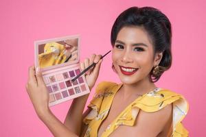 retrato de uma mulher com maquiagem e escova cosmética