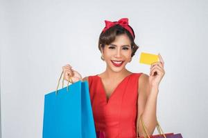 mulher elegante com sacola de compras e cartão de crédito foto