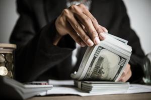 close-up de mãos de uma empresária segurando notas de dólar