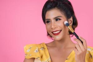 retrato de uma mulher com pincel de maquiagem