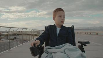 menino em uma cadeira de rodas lá fora