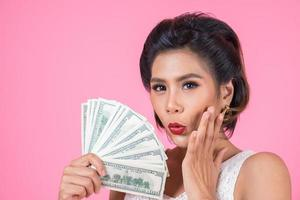 mulher bonita feliz segurando dólares foto