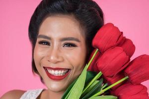retrato de uma linda mulher com um buquê de flores de tulipa vermelha foto