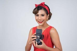 Fotógrafa feliz e elegante segurando uma câmera retro vintage