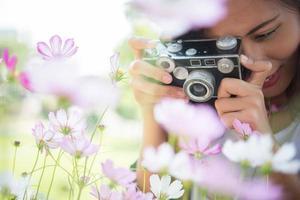 garota hipster com foco de câmera vintage atirando flores em um jardim