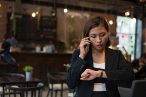 linda mulher de negócios falando no celular, olhando para a mão assistir sobre o fundo do café